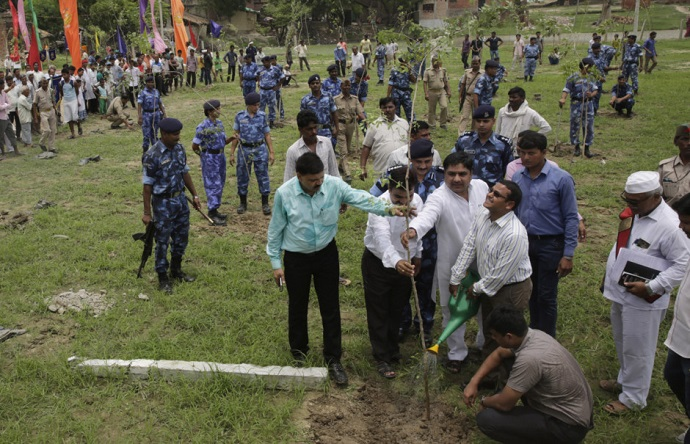 Indian government officials water a saplings after planting on the outskirts of Allahabad, India, Monday, July 11, 2016. Hundreds of thousands of people in India's most populous state Uttar Pradesh are jostling for space as they attempt to plant 50 million trees over the next 24 hours in hopes of setting a world record. (AP Photo/Rajesh Kumar Singh)