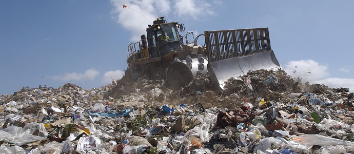 An Excavator at dumping ground against sky